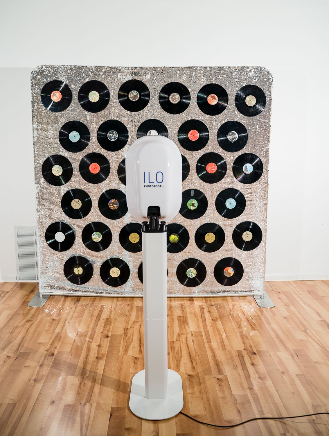 a memphis photo booth rental, ILO Photo Booth, in front of a custom made backdrop for a music theme featuring vinyl records on a sequins backdrop