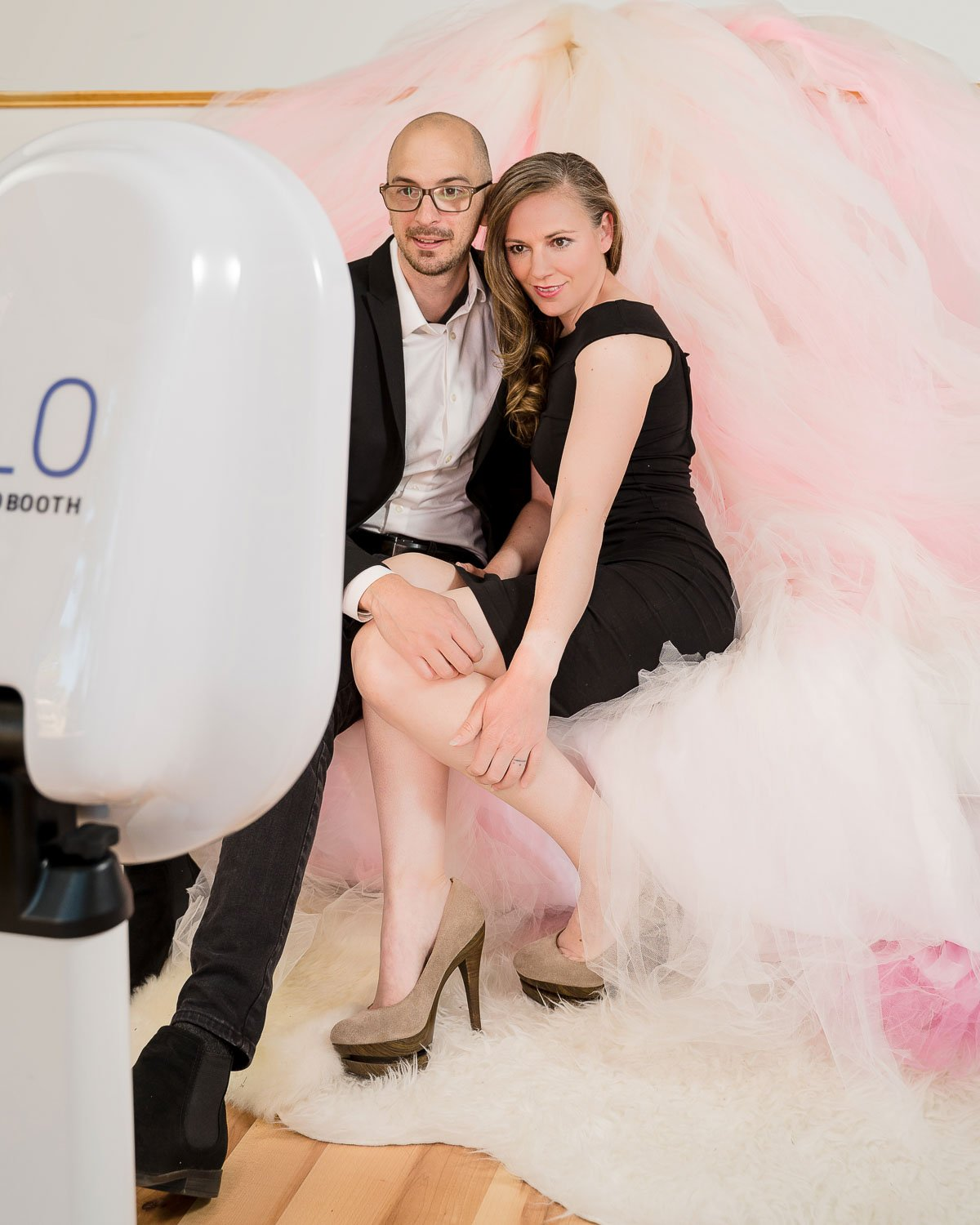 a couple sitting in front of a photo booth with custom made tulle backdrop
